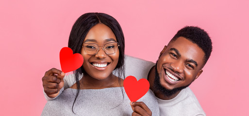 Portrait of black couple in love with heart shaped cards