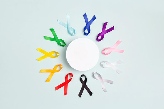 Circle of  colorful awareness ribbons with place for text on blue background. World cancer day concept, February 4.