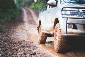 Dirty offroad car, SUV covered with mud on countryside road, Off-road tires,  offroad travel  and driving concept. Wall mural