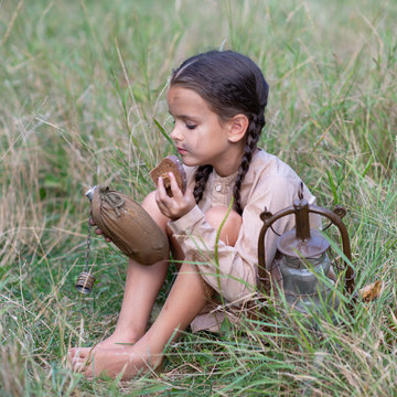 Little girl with long pigtails and beautiful dirty face sitting at summer meadow with vintage paraffin stove and eating stale bread. Orphan, child of war, poverty, hunger, famine, poor destitute kid.