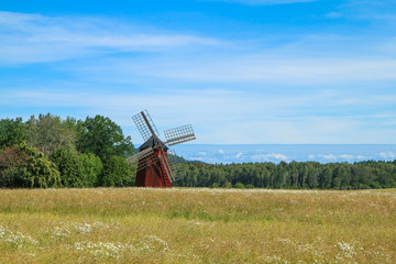 Foto op Canvas Molens The typical red Swedish windmill standing in the fields full of grain. The rural landscape of the Swedish countryside.