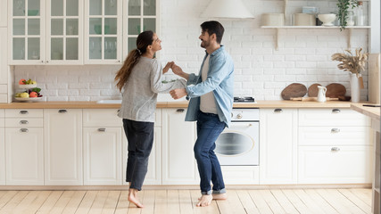 Photo sur Plexiglas Ecole de Danse Happy family couple dancing barefoot on wooden floor in kitchen.