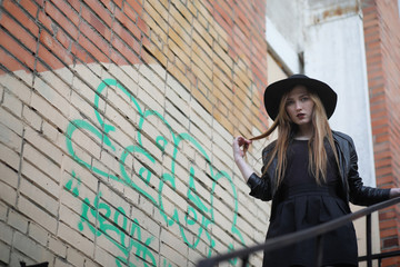 A girl walks down the city street in a leather waistcoat with a phone. Young beautiful girl in a hat and with a dark make-up outside. Girl in the Gothic style on street. Wall mural