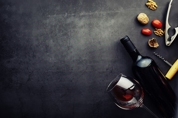 Wall Murals Wine Wine glass and black wine bottle. Nuts cheese and tomatoes for snack.