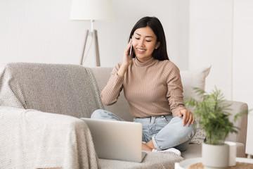 Multitasking concept. Girl using laptop and talking on cellphone