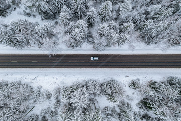 Aerial view of winter road with a car and snow covered forest in Finland