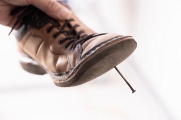 釘が刺さった靴