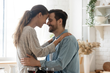 Happy loving mixed race couple enjoying sweet moment in kitchen.
