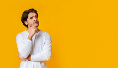 Doubtful man thinking about something, touching chin with thoughtful face expression