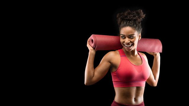 Cheerful black girl in sportswear holding yoga mat