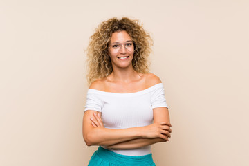 Young blonde woman with curly hair over isolated background with glasses and happy