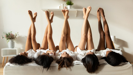 Diverse girls lie upside down celebrate hen party