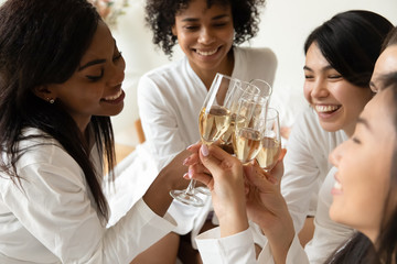 Smiling diverse friends have fun enjoying hen party at home