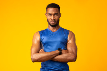 Afro sportsman with folded arms at studio