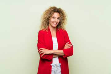 Young blonde woman with curly hair over isolated green background keeping the arms crossed in...