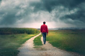 Man in red jacket walks alone on rural road with dark cloudy sky. Fotomurales