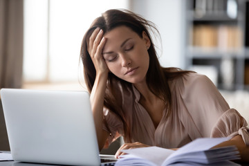 Tired young woman fall asleep working at laptop