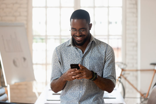 Smiling biracial male employee using cellphone in office boardroom