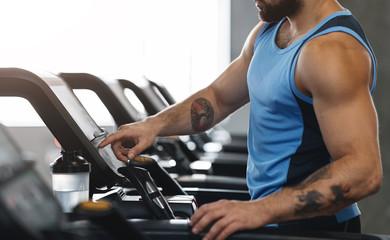 Athlete turning on modern treadmill at gym, panorama