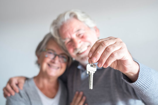 couple of two seniors after buy a new house or car and go to live together - man holding a key and mature man and woman looking at it