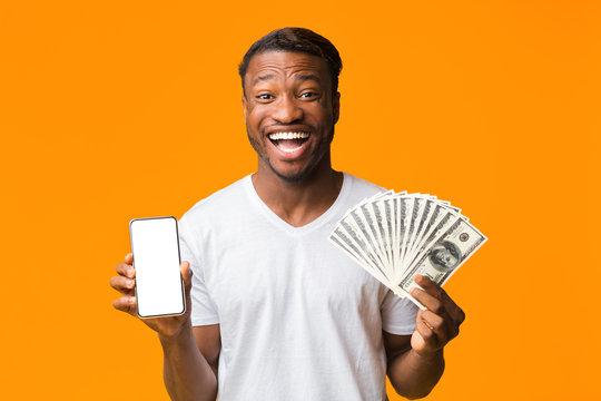 Excited Black Man Holding Smartphone And Money On Orange Background