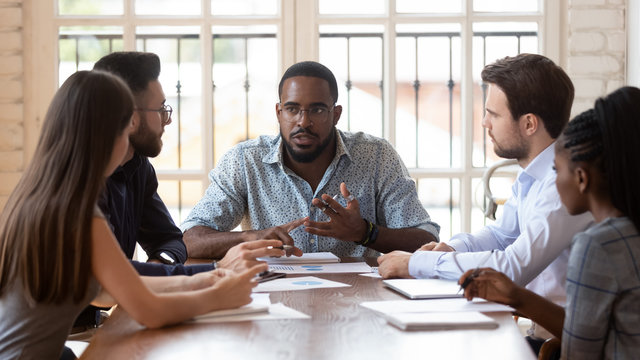 Multinational millennial colleagues gather at office meeting