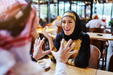 Stunning laughing arab woman dressed in traditional wear sitting in cafe with her beloved husband. Saturday morning is the best time to spend quality time with loved ones. Diversity concept.