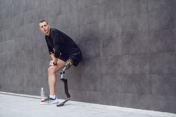 Fotomurales - Full length of handsome caucasian sportsman with artificial leg leaning on wall and resting from running. Next to him is bottle with refreshment.