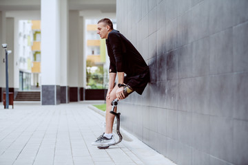 Fotomurales - Full length of handsome caucasian sportsman with artificial leg leaning on wall and resting from running.