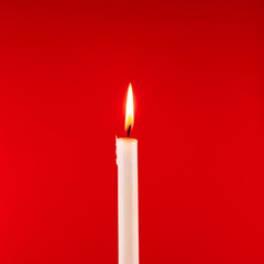 Burning candle on a red background. Square image.