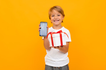 Caucasian boy holds white box with gift and phone, portrait isolated on blue background