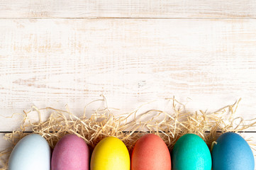 Easter concept. Colorful eggs on white wooden background with copy space for text. Top down view or flat lay