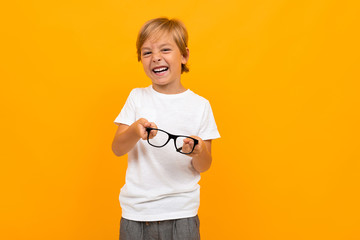 new vision concept. boy in a white T-shirt squints holding glasses in his hands on a yellow...