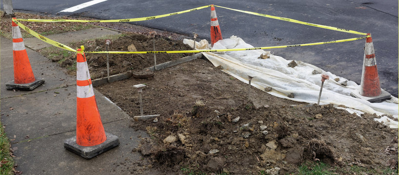 Early stage of sidewalk handicapped ramp construction in urban neighborhood.