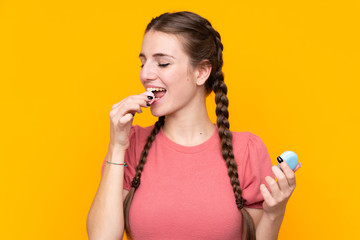 Printed kitchen splashbacks Macarons Young woman over isolated yellow background holding colorful French macarons and eating it