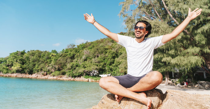 Cheerful latin young man in white T-shirt and sunglasses  with arms spread opened sitting at the tropical beach, Happiness, freedom of vacation and travel concept.