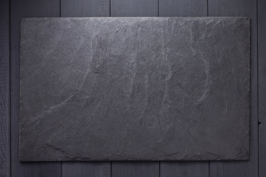 slate stone nameplate or wall sign at wooden background