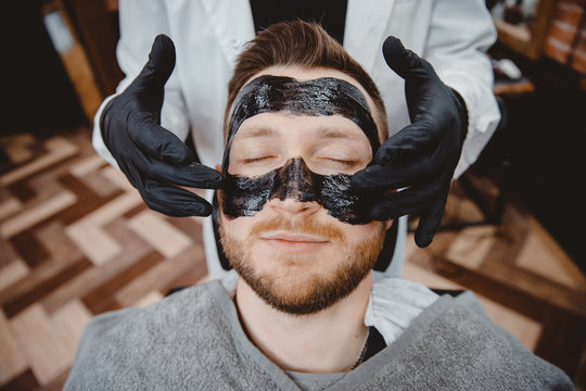 Spa and skin care for men. Barber professional applies black charcoal mask to client man