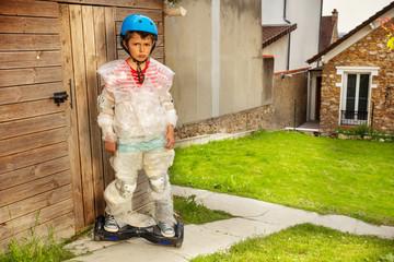 Sad hoverboard boy in overprotective bubble wrap