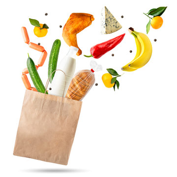 Food flies out of a paper bag on a white, isolated. Shopping supermarket.