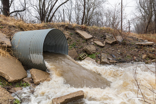 Closeup motion blur of storm water runoff flowing through metal drainage culvert under road. January storms brought heavy rain and flash flooding to Illinois