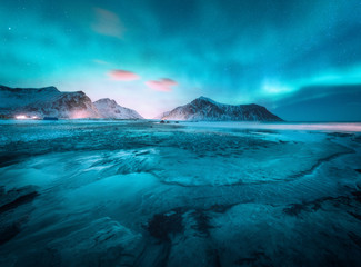 Stores photo Bleu jean Aurora borealis above the snowy mountain and sandy beach in winter. Northern lights in Lofoten islands, Norway. Starry sky with polar lights. Night landscape with aurora, frozen sea coast, city lights