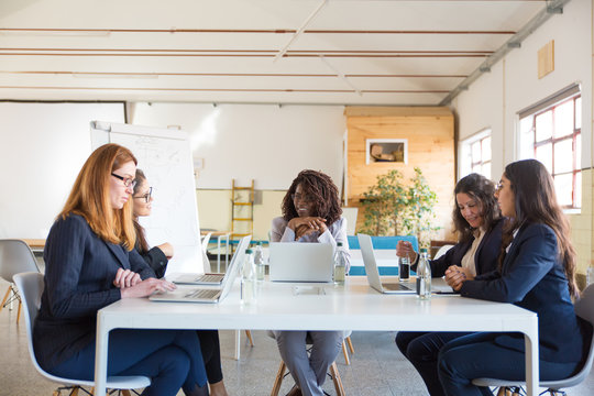 Businesswomen sitting at table in office. Group of professional smiling multiethnic businesswomen sitting around table in meeting room. Women in business concept