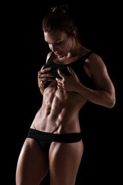 Fitness woman showing abs and flat belly, isolated on black background. Athletic girl shaped abdominal