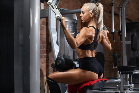 Fitness woman doing exercise for back lat pulldown in gym. Athletic girl workout