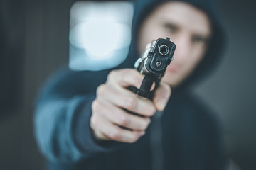 Crime or robbery concept: Man with black gun is aiming with his weapon - fototapety na wymiar