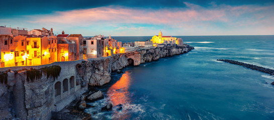 Dramatic evening cityscape of Vieste - coastal town in Gargano National Park, Italy, Europe. Splendid spring sunset on Adriatic sea. Traveling concept background. Fotomurales