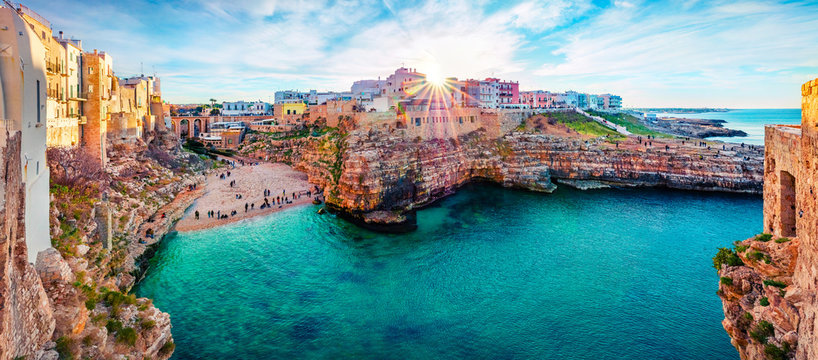 Panoramic spring cityscape of Polignano a Mare town, Puglia region, Italy, Europe. Marvelous evening view of Adriatic sea. Traveling concept background.