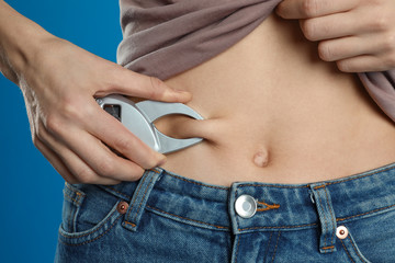 Young woman measuring body fat with caliper on blue background, closeup