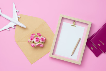 Mockup picture frame for travel with valentines day & love season background concept. Top view of mock up photo frame with craft rose in envelope, passport, airplane model on pink background.